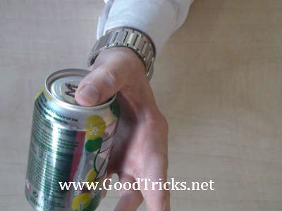 Coin is secretly slid onto top of can.