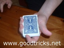 Deck is held pointing towards spectator. Thumb on oneside, first finger at top of deck.