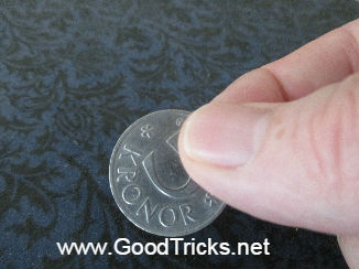 Coin being held between finger and thumb in preparation for a magic coin trick.