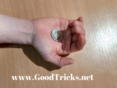 Fingers curl in to palm to allow the coin to fall into position..