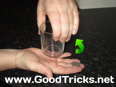 Image showing coin in new position near finger tips, raedy to be thrown up into the glass.