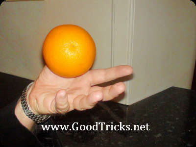 An orange appears to float above your hand.