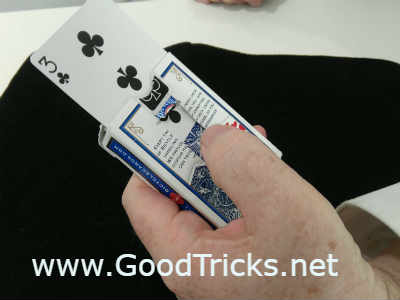 Hold out card in front of spectator and push up card with thumb.