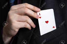 Magician reaching into pocket for ace of hearts playing card. Magic trick image.